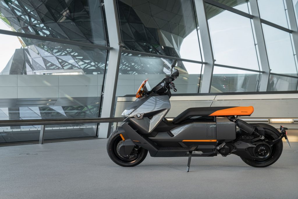 The side view of a gray-and-orange 2022 BMW CE 04 by a steel-and-glass building