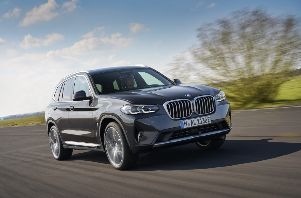 A dark-gray metallic 2022 BMW X3 xDrive30e luxury compact SUV travels on a country road along green hills
