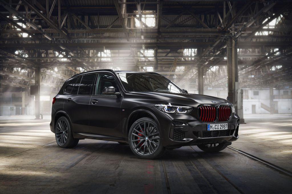 A 2022 BMW X5 Black Vermilion Edition luxury SUV parked in a sun-dappled warehouse
