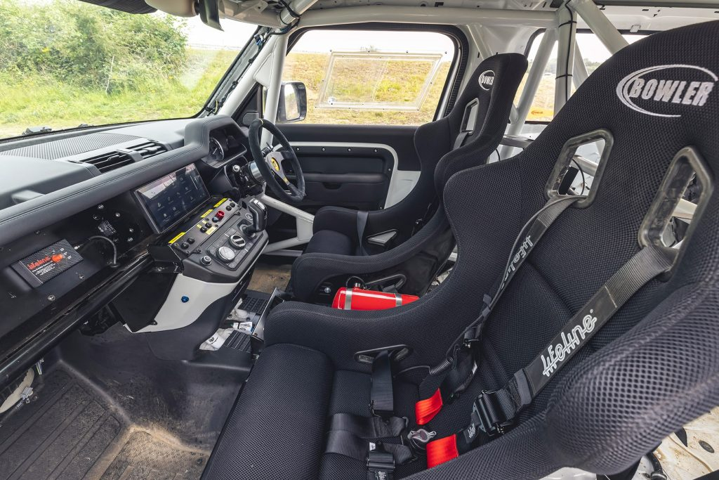 The racing seats, roll cage, and dashboard of a 2022 Bowler Land Rover Defender 90 Challenge