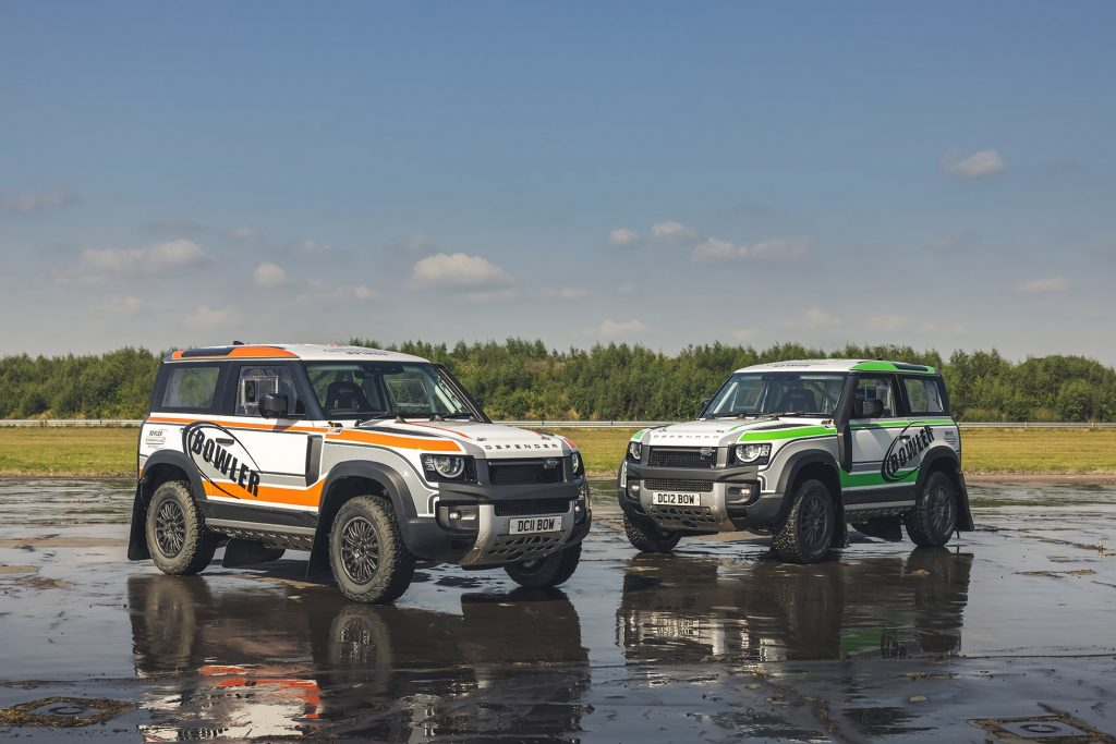 An orange-and-white and green-and-white 2022 Bowler Land Rover Defender 90 Challenge racer on a wet airstrip