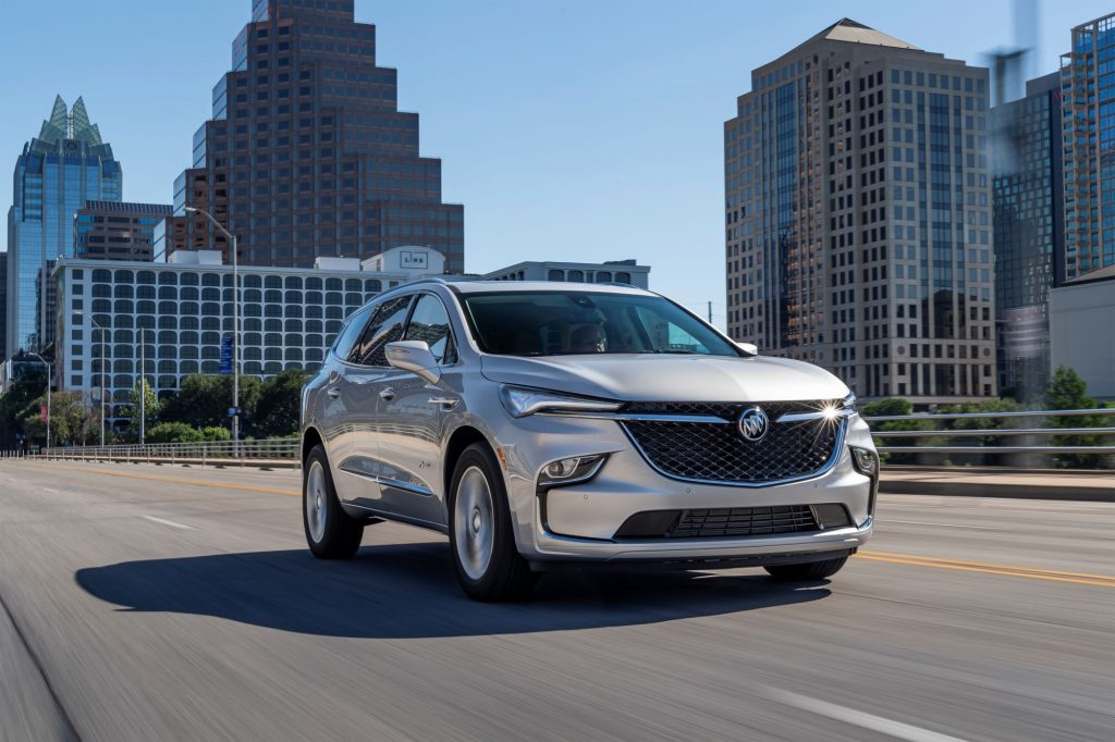 A silver 2022 Buick Enclave driving through a city surrounded by sky scrapers driving on a highway.