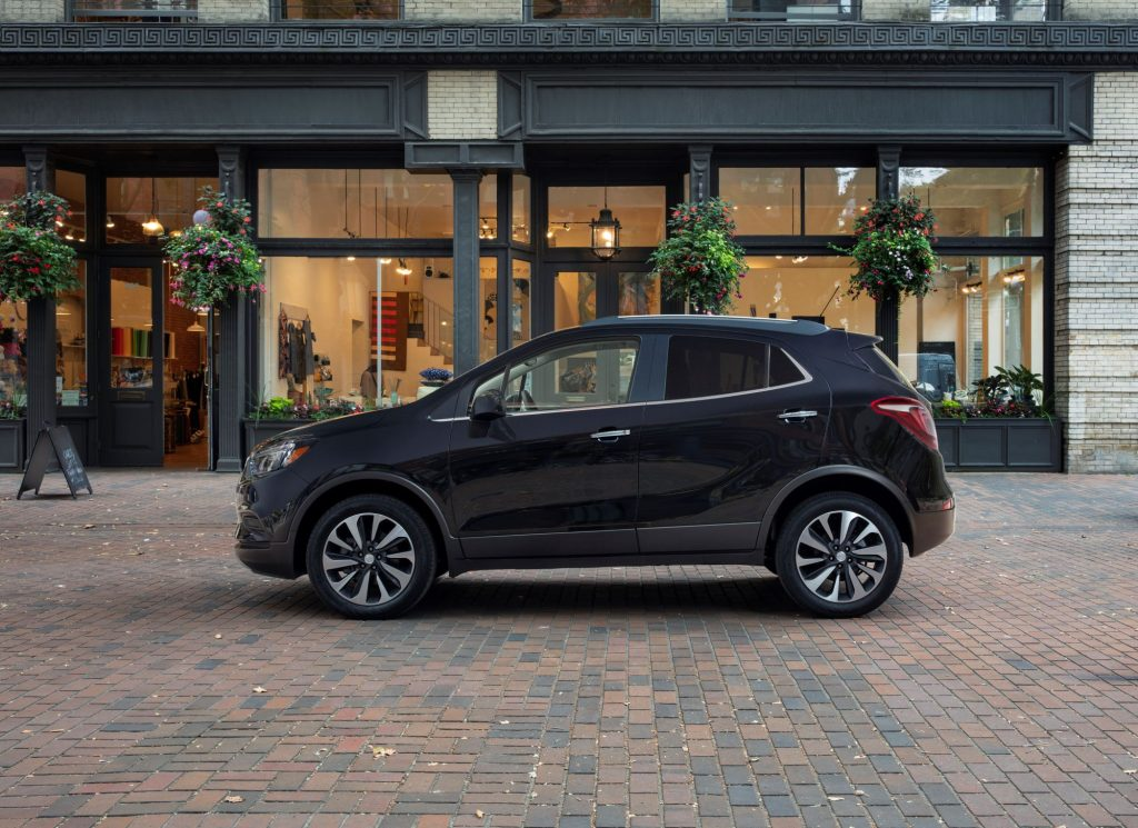 A 2022 Buick Encore compact SUV model parked near a store on a cobblestone road
