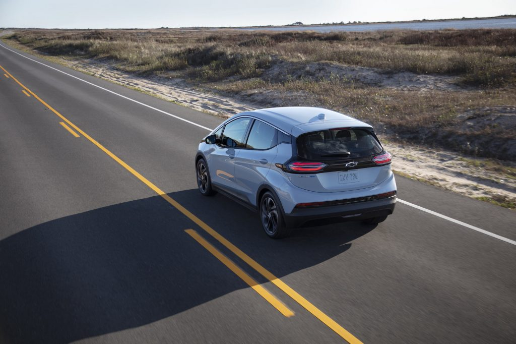 A silver 2022 Chevy Bolt EV travels on a two-lane highway along a large body of water on a sunny day