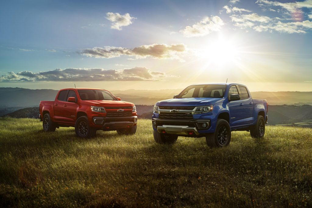 Two 2022 Chevrolet Colorado Trail Boss pickup trucks parked on a grassy hill with the sun and mountains behind them