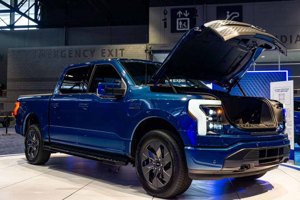 A blue 2022 Ford F-150 Lightning front 3/4 with open frunk at the 2021 Chicago Auto Show