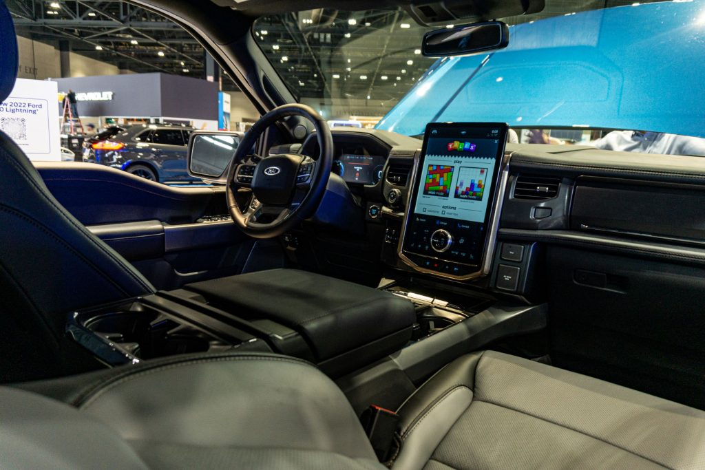 The front interior of a 2022 Ford F-150 Lightning with its folding table deployed at the 2021 Chicago Auto Show