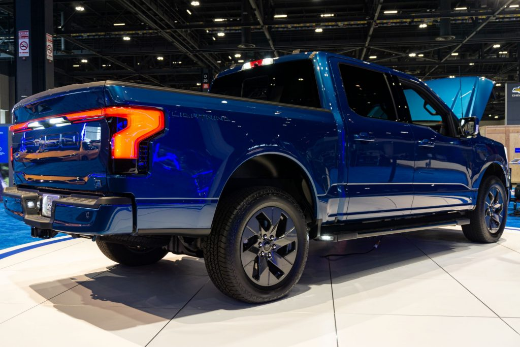 The rear 3/4 view of a blue 2022 Ford F-150 Lightning with its frunk open at the 2021 Chicago Auto Show