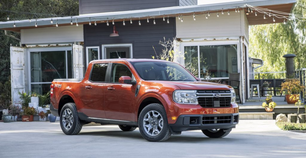 An orange 2022 Ford Maverick parked in front of a house with vintage bulb lights hanging above it, the 2022 Ford Maverick is a hybrid truck