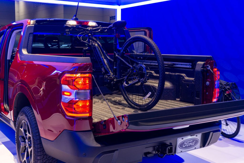 The bed of a red 2022 Ford Maverick Lariat with a black mountain bike mounted inside
