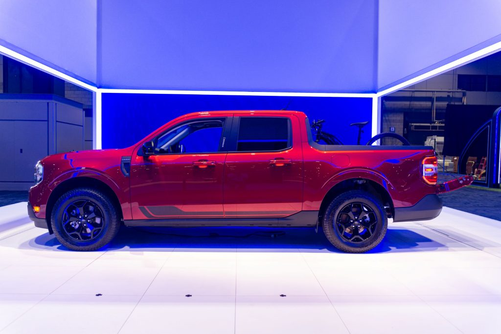 The side view of a red 2022 Ford Maverick Lariat with a bike in the bed at the 2021 Chicago Auto Show