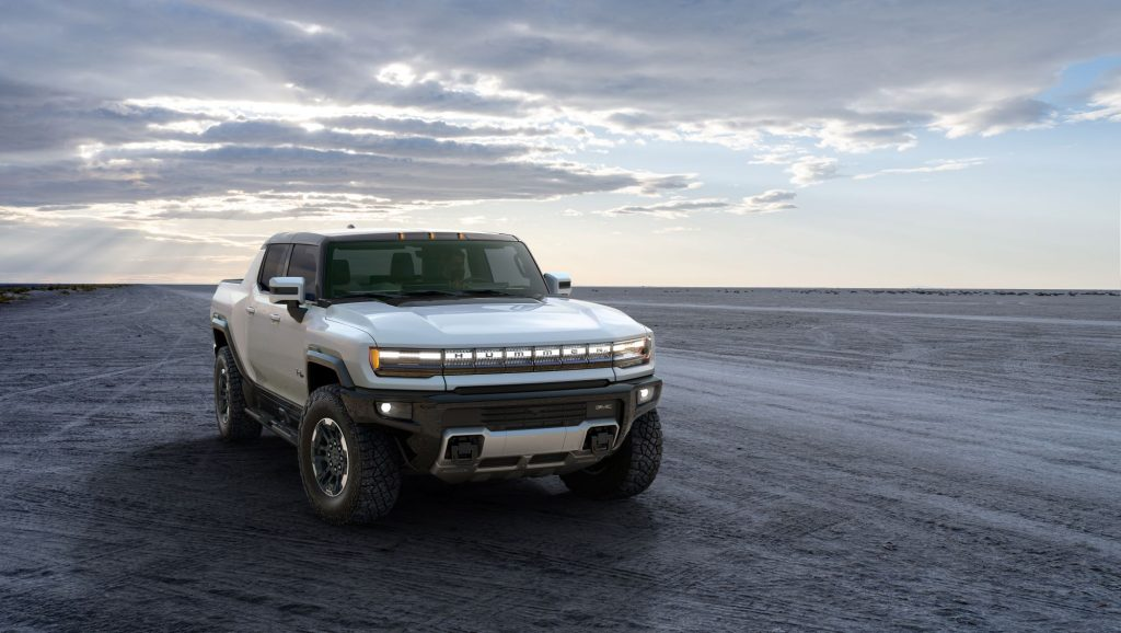 A white 2022 GMC Hummer EV sitting on flat dirt with a cloudy sunset behind it.