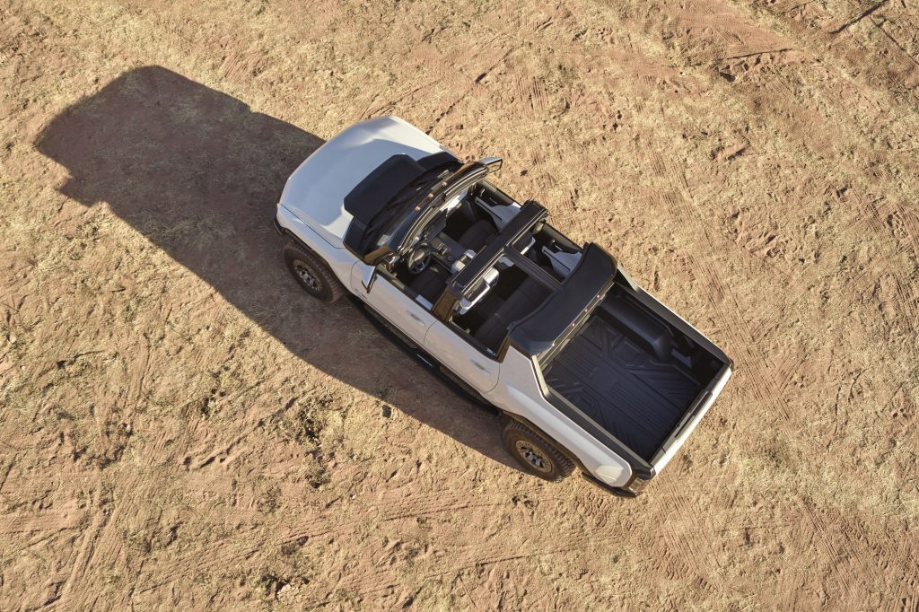 An overhead view of the 2022 GMC Hummer EV, parked on an expanse of beige dirt, with its roof removed