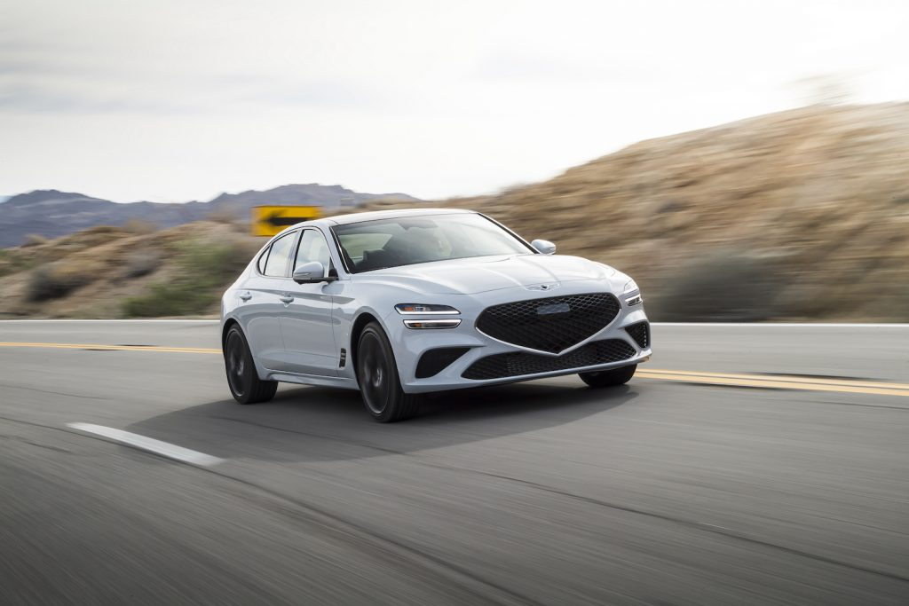 A white 2022 Genesis G70 rounding a curve on an empty road, the G70 is one of the best affordable AWD sedans of 2021