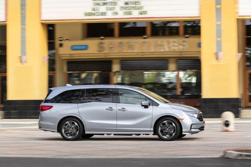 A gray 2022 Honda Odyssey minivan driving past a movie theater
