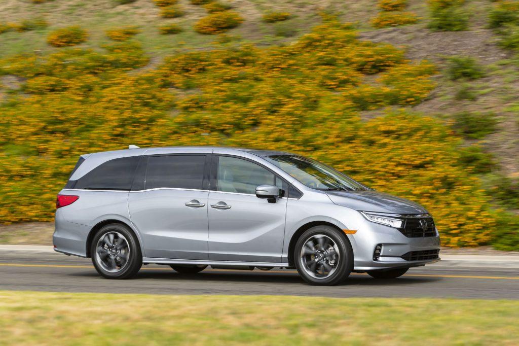 A gray 2022 Honda Odyssey minivan driving on a highway near a grassy hill