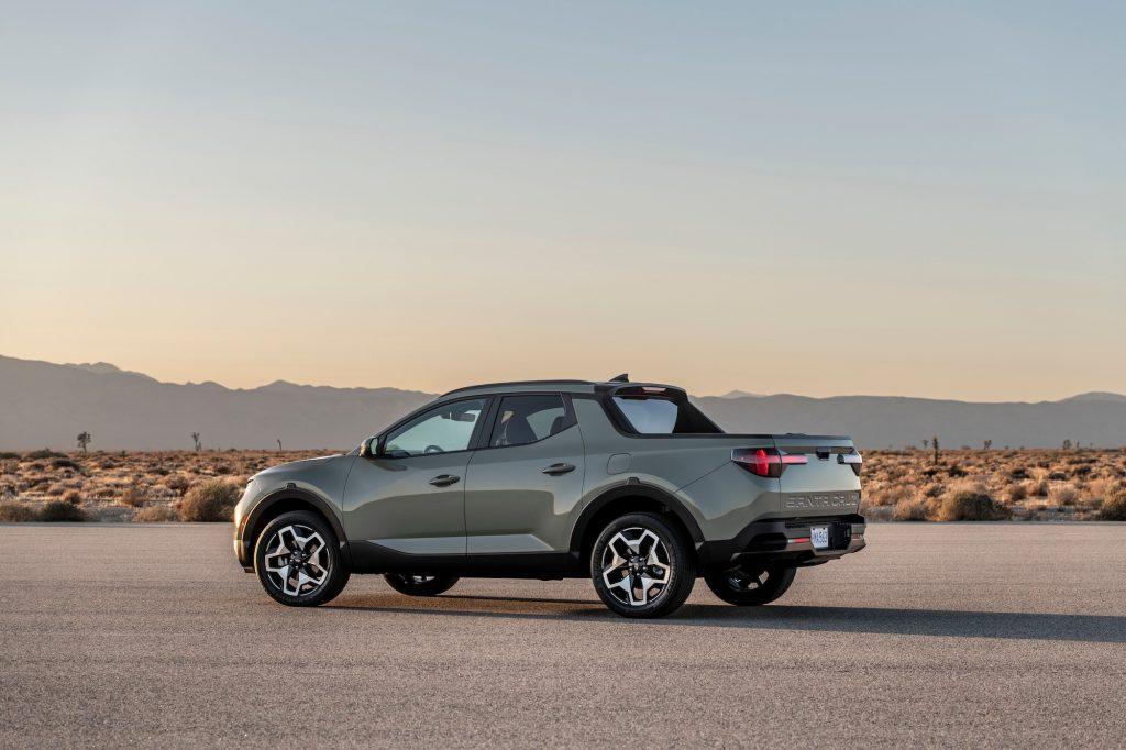 A silver 2022 Hyundai Santa Cruz parked on asphalt in a desert with mountains in the distance