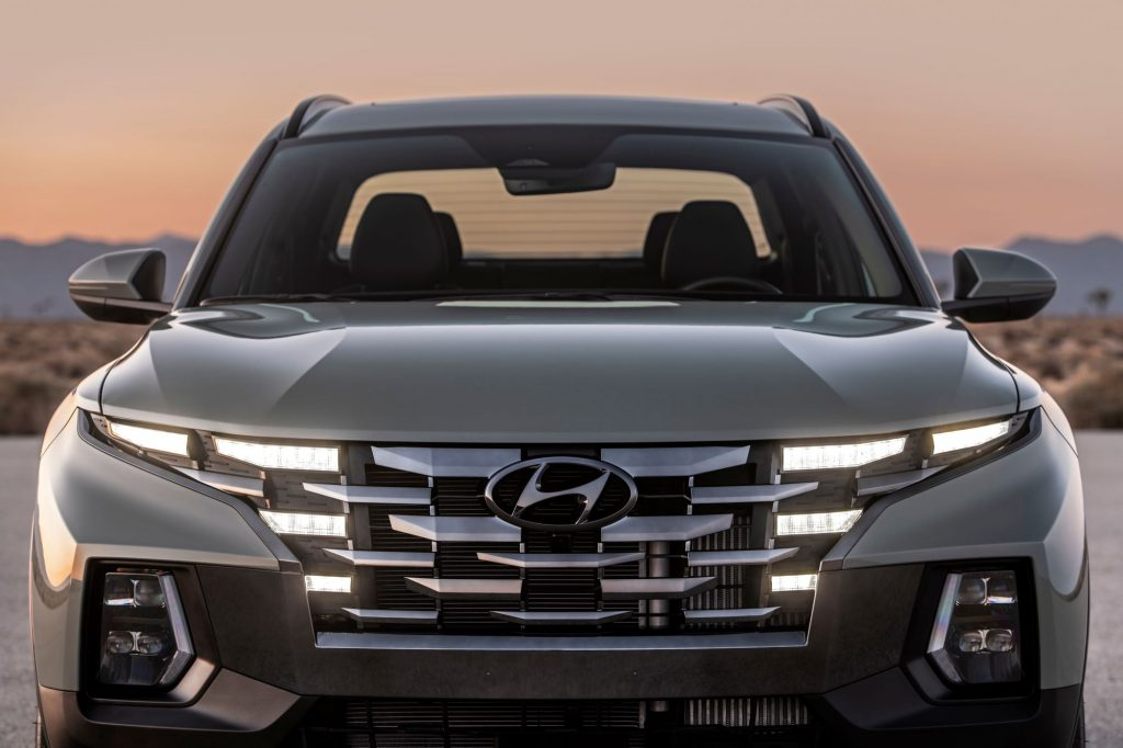 A front exterior shot of the 2022 Hyundai Santa Cruz with its headlights and grille lit up