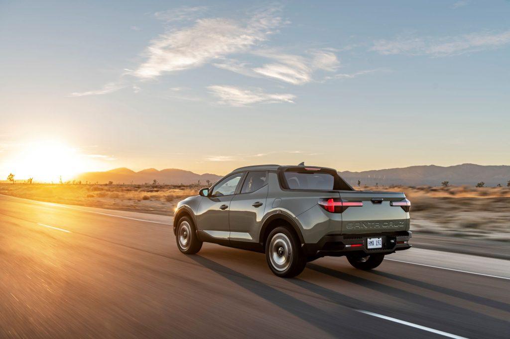 The 2022 Hyundai Santa Cruz pickup truck driving down a country highway as the sun rises