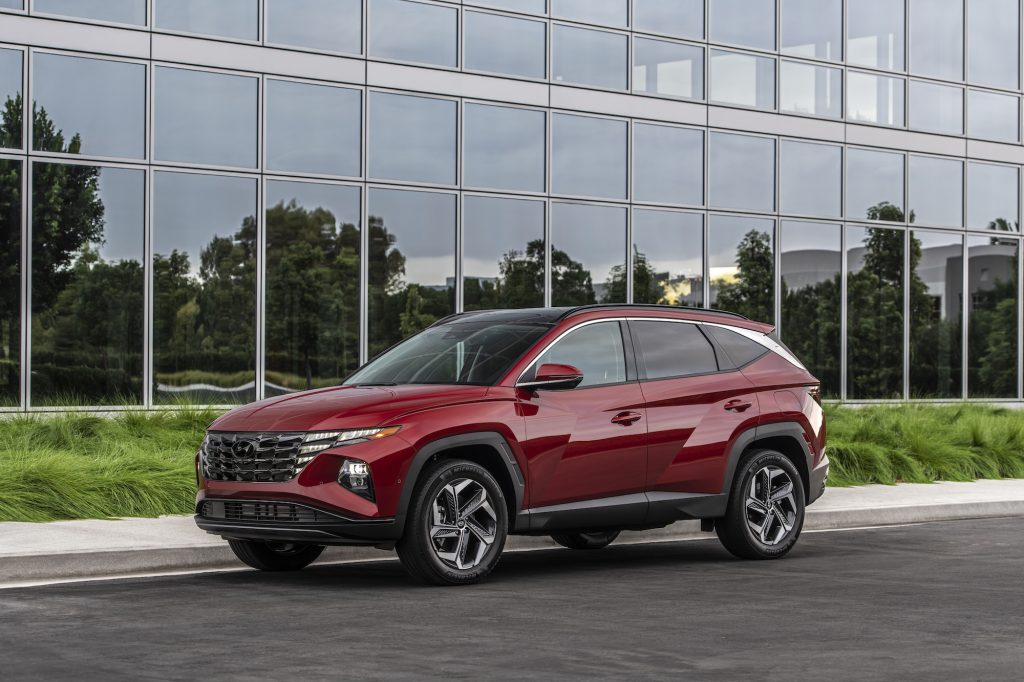 A red metallic 2022 Hyundai Tucson compact SUV parked outside a glass building