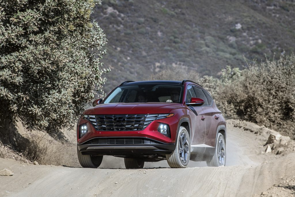 A dark-red metallic 2022 Hyundai Tucson compact SUV parked on a dusty mountain road