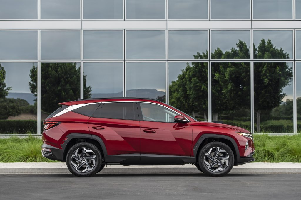 A cherry-red metallic 2022 Hyundai Tucson parked on the street outside a glass buildin