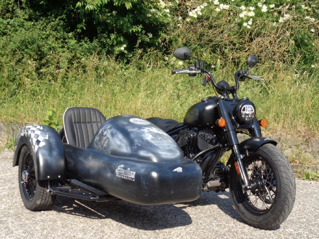 A black 2022 Indian Chief Bobber with Iwan Bikes' BellaVista sidecar parked by the side of the road