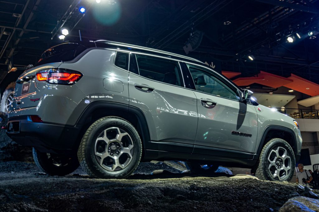 The side 3/4 view of a gray 2022 Jeep Compass Trailhawk on a simulated gravel rise