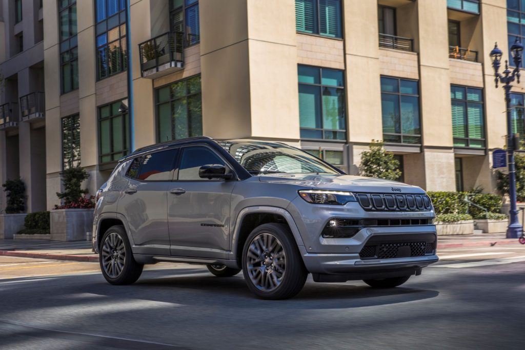 A silver 2022 Jeep Compass with High Altitude Package drives through a city