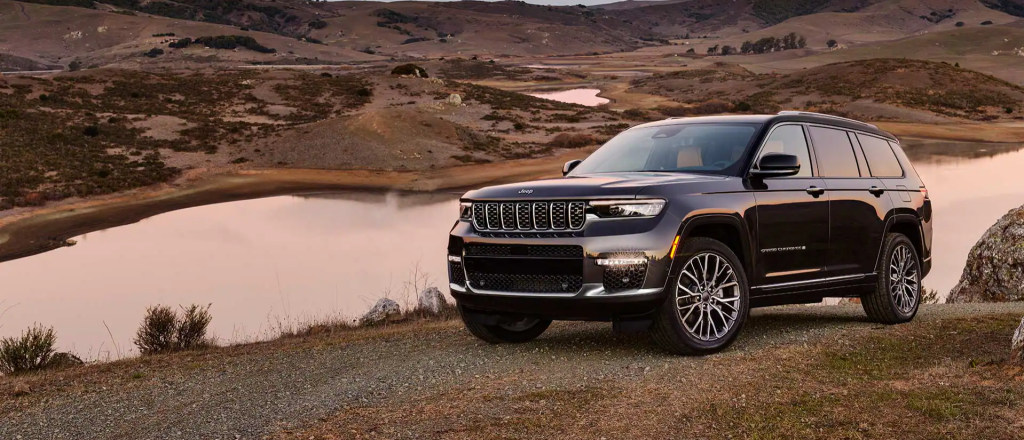 The 2022 Jeep Grand Cherokee L SUV model parked on a hill near a river