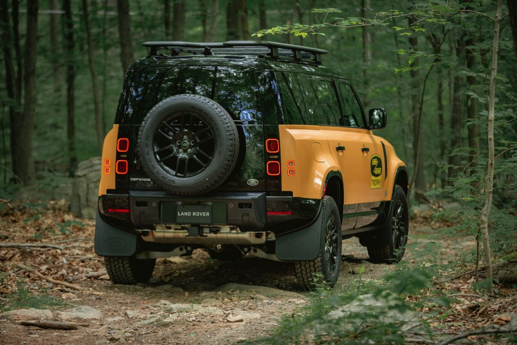 The rear 3/4 view of a yellow-and-black 2022 Land Rover Defender Trophy Edition in a forest