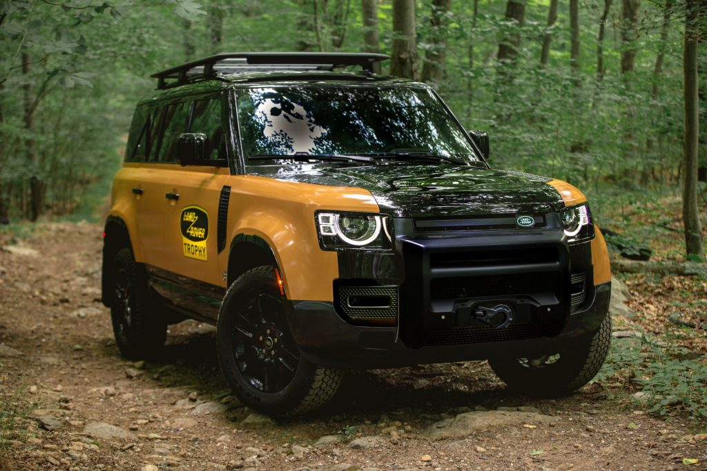The yellow-and-black 2022 Land Rover Defender Trophy Edition with optional winch in a forest