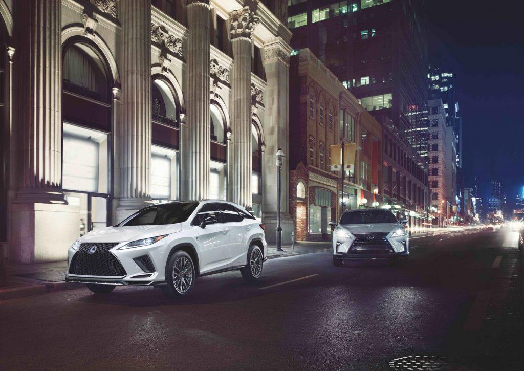 Two 2022 Lexus RX450h luxury midsize SUVs on a city street at night