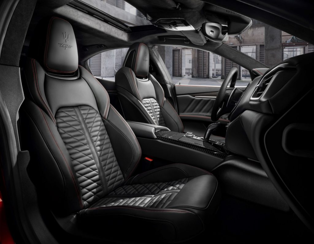 The red-stitched black-leather front sport seats and carbon-fiber-trimmed center console of the 2022 Maserati Ghibli Trofeo sedan