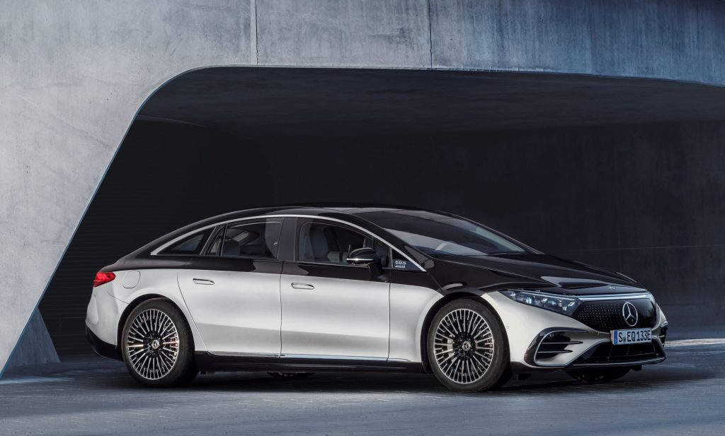 A silver-and-black 2022 Mercedes-Benz EQS electric sedan by a concrete building