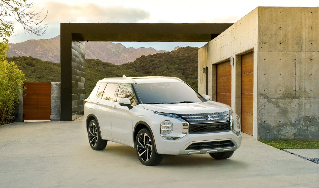 A white 2022 Mitsubishi Outlander SUV parked out of a luxury home in the mountains