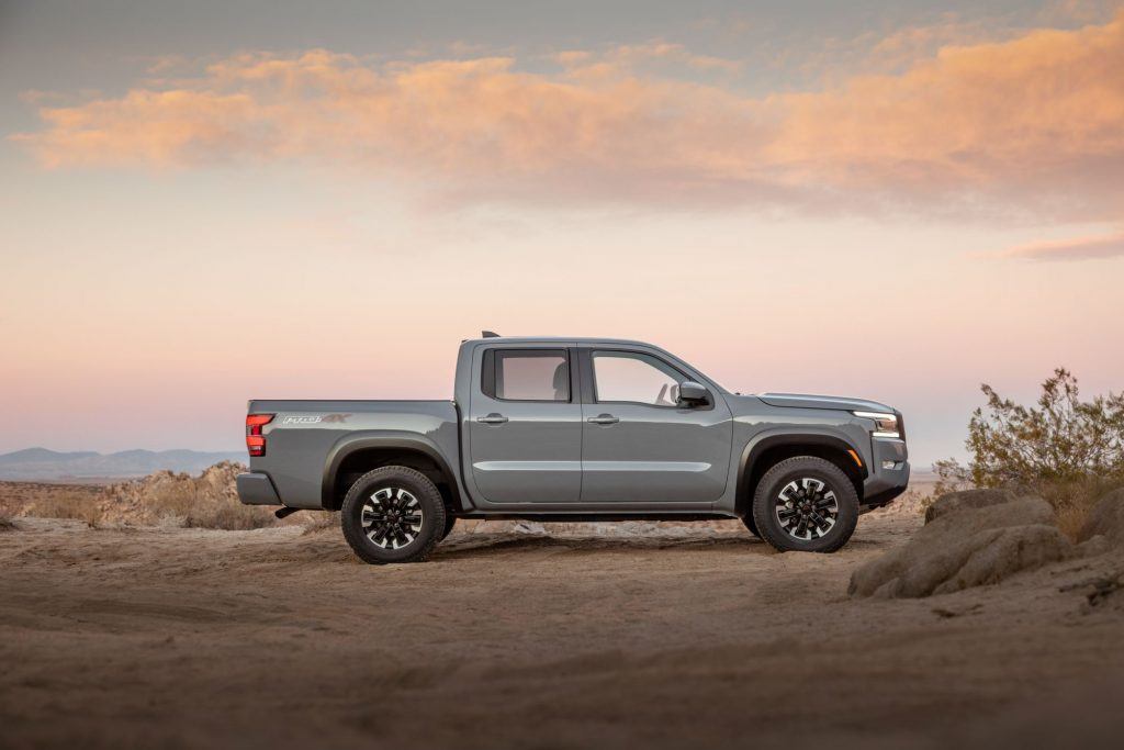 A Silver Nissan Frontier in a desert area with a slightly cloudy sunset colored sky in the background.