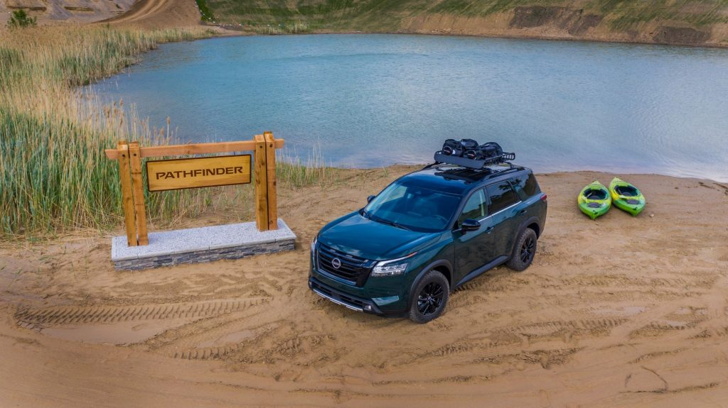 A blue 2022 Nissan Pathfinder sits in front of a pond on a dirt spot between a wooden sign with a concrete base that reads 'Pathfinder' and two kayaks that are light green in color.