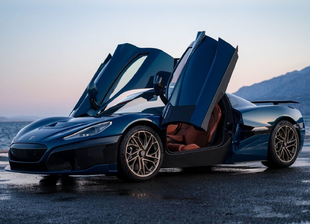 A dark-blue 2022 Rimac Nevera electric supercar with its doors up parked by the ocean