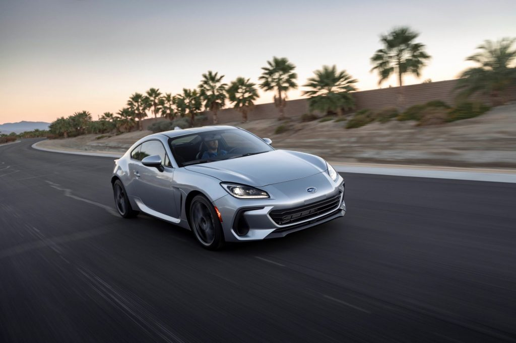 A silver 2022 Subaru BRZ driving down a road in a desert tropical area with sand and palm trees.