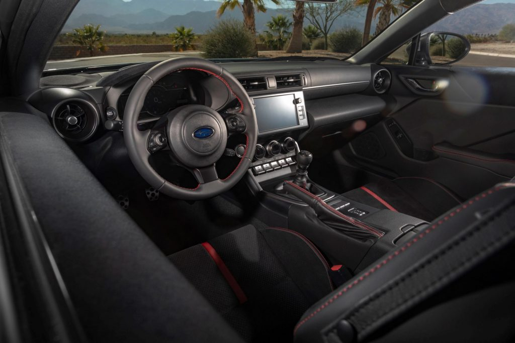 The black-and-red front seats and dashboard of a manual 2022 Subaru BRZ