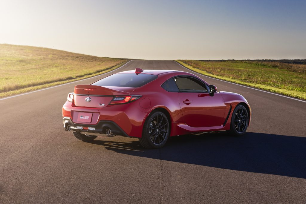 A red 2022 Toyota GR 86 sports car parked on a strip of asphalt running through rolling green hills on a sunny day