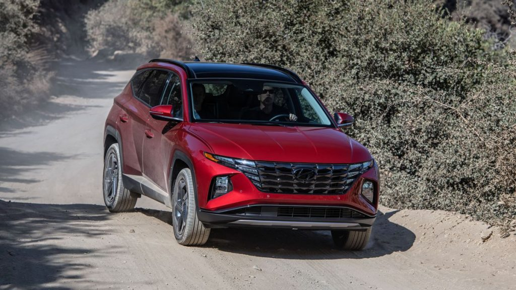 A red 2022 Hyundai Tucson driving on a dirt road