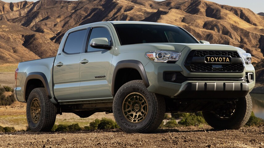 a 2022 Toyota Tacoma pickup truck parked in the dirt near mountains