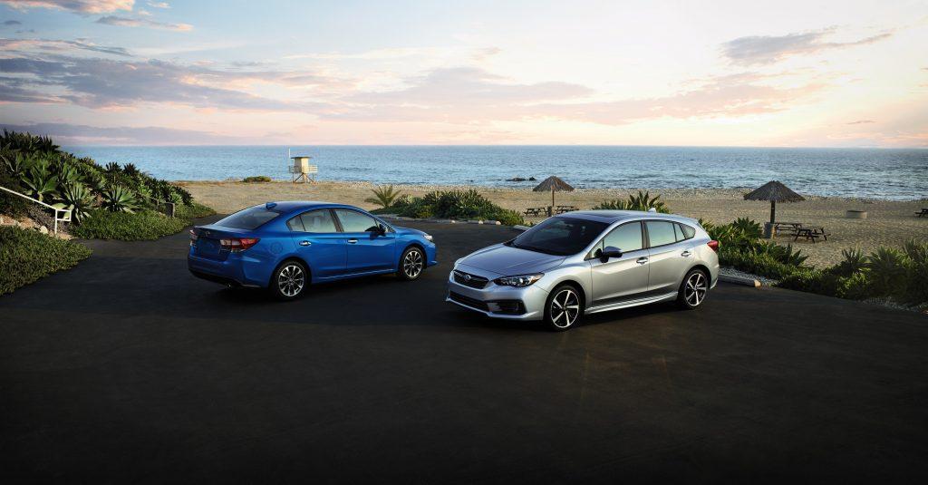 A blue Impreza sedan and a silver wagon on the beach