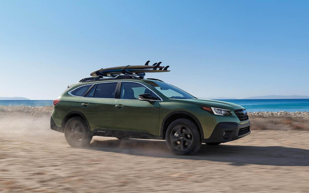 A green 2021 Subaru Outback with surfboards on top.
