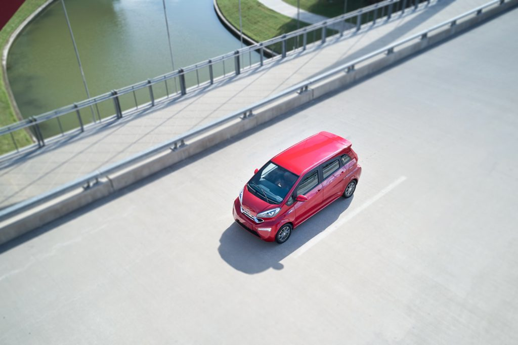 A bright red Kandi K23 EV on the open road