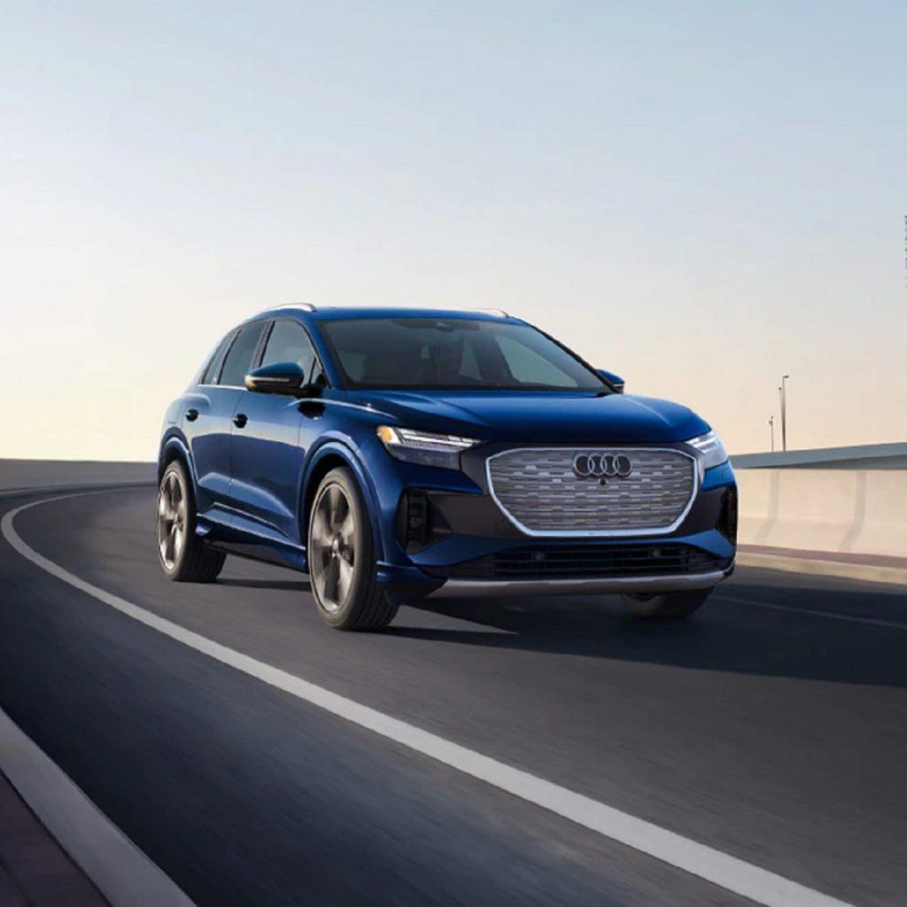 A blue 2021 Audi e-Tron driving down a road.