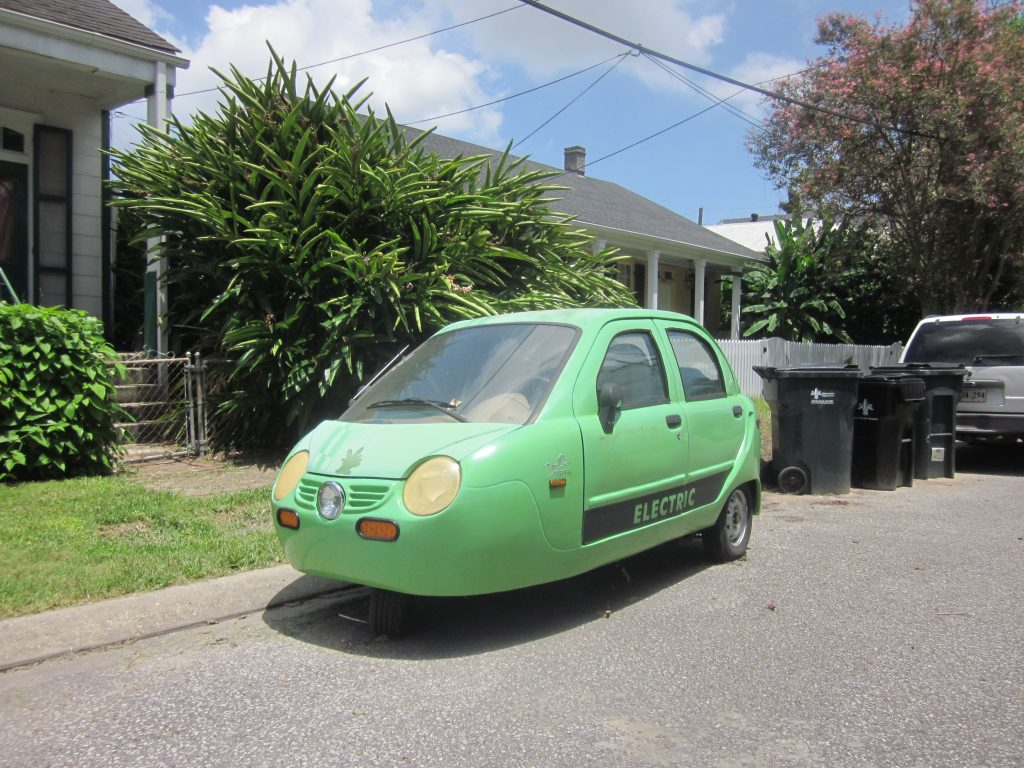 A green ZAP! Xebra parked on the side of the road