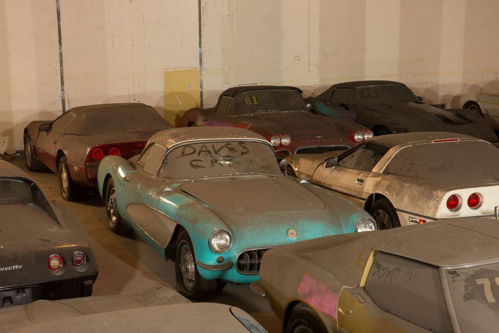 A dust-covered turquoise 1956 Chevrolet Corvette amongst several dust-covered Lost Corvettes